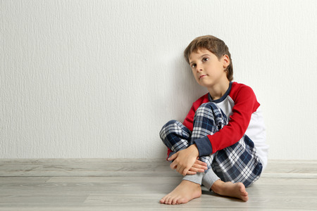 Cute little boy sitting on floor in empty room