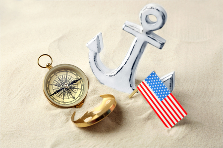 Anchor, compass and USA flag in sand. Columbus Day concept Stock Photo