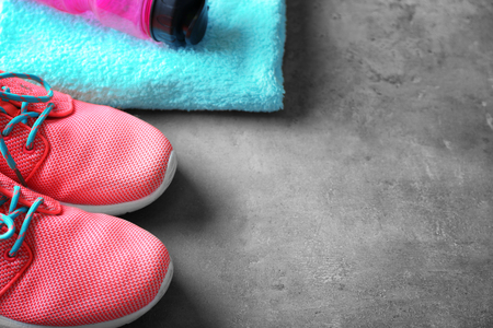Sport shoes, bottle of water and towel on grey table closeup