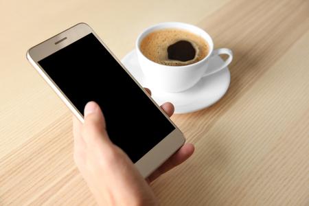 Man using smart phone in cafe Фото со стока