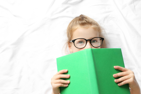 Funny little girl lying on bed with book Stock Photo