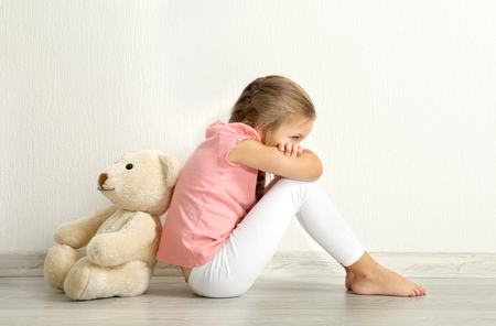 Sad little girl with teddy bear sitting on floor in empty room