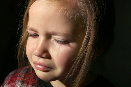 Portrait of crying little girl on black background