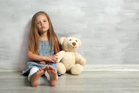 Cute little girl with teddy bear sitting near grey wall