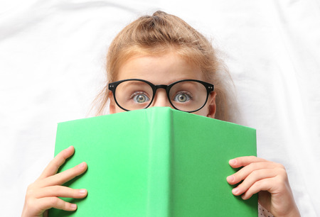 Cute girl with book lying on white sheets