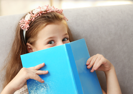 Cute girl reading book on couch