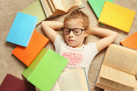 Cute girl with books lying on floor