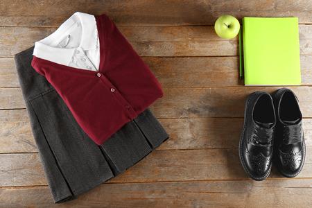 School uniform on wooden background, flat lay