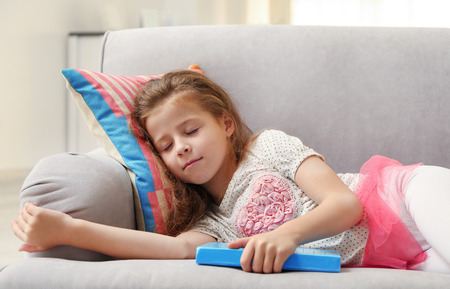 Cute girl with book on couch