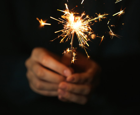 Female hands holding sparkler on dark background, close up