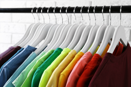 Colorful t-shirts on hangers against light background, close up view 스톡 콘텐츠