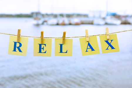 Cards with printed word RELAX on river background