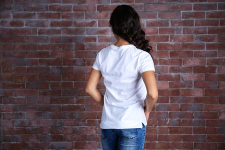 Young woman in blank white t-shirt standing against brick wall