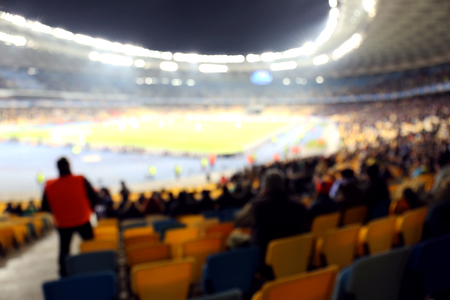 Fans watching football game at stadium, blurred background