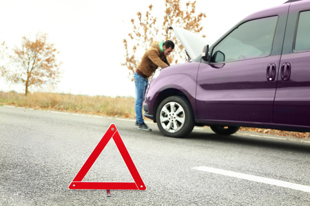 Traffic warning sign on road with car and driver on background