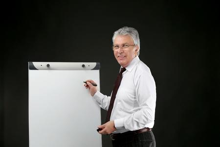 Senior businessman with flip chart on black background