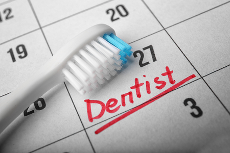 Word DENTIST in calendar and tooth brush, closeup