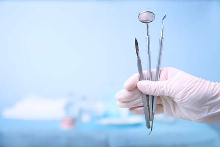 Dentist holding set of medical tools on blurred background