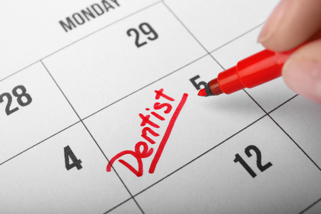 Human hand writing word DENTIST in calendar, closeup