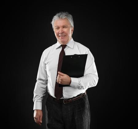 Senior businessman with clipboard on black background Foto de archivo