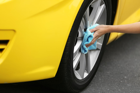 Female hand cleaning car wheel, closeup