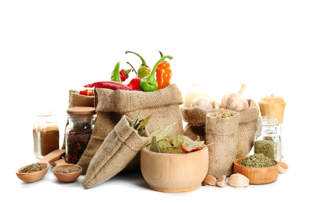 Spices in sacking bags on white background