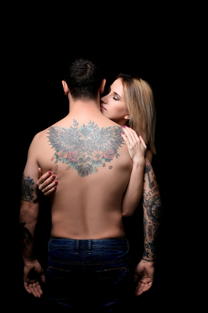 Sexy woman hugging tattooed man on black background Standard-Bild - 109932458