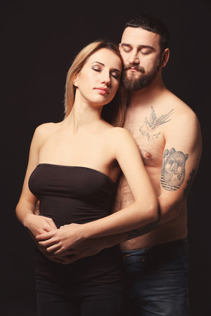 Portrait of romantic tattooed couple on black background