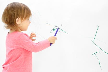 Śliczna mała dziewczynka rysująca na jasnej ścianie