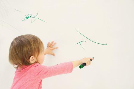 Bambina sveglia che attinge parete chiara Archivio Fotografico