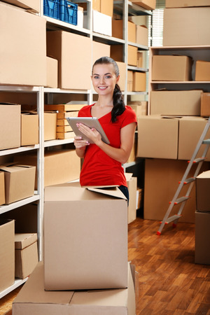 Young businesswoman with tablet at warehouse