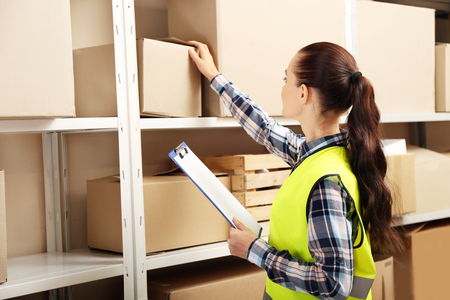 Young businesswoman with clipboard at warehouse Foto de archivo