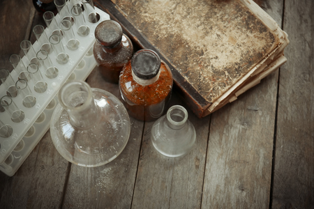 Vintage equipment of chemical laboratory on wooden background, closeup Imagens