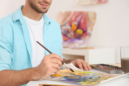 Young male artist painting picture in studio, close up