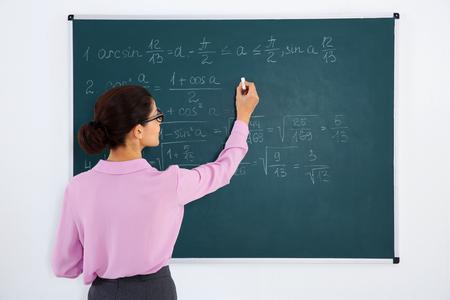 Young female teacher beside blackboard on white background Stock Photo