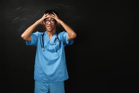 Young handsome medical student on blackboard background