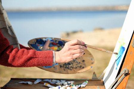 Senior female artist painting picture near river, close up Imagens