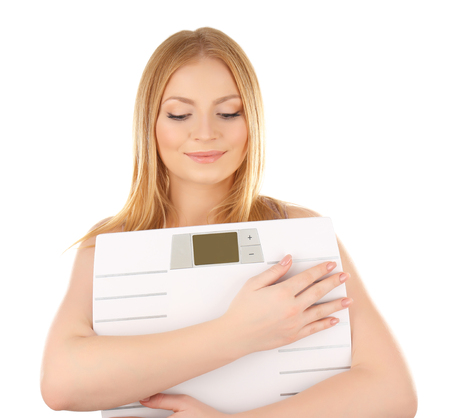 Young woman with scales on white background