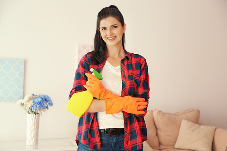 Young cleaner with spray bottle in room