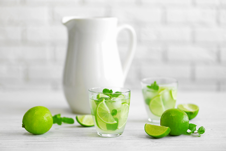 Fresh lime cocktail on brick wall background