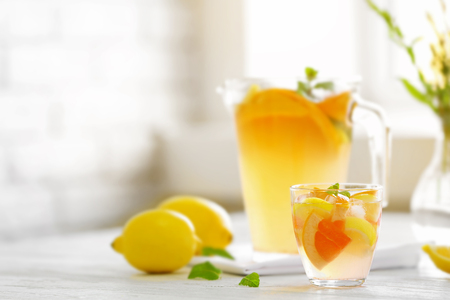 Citrus cocktail on table on blurred window background