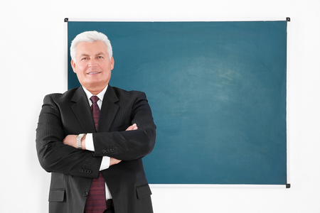 Senior teacher beside blackboard on white background