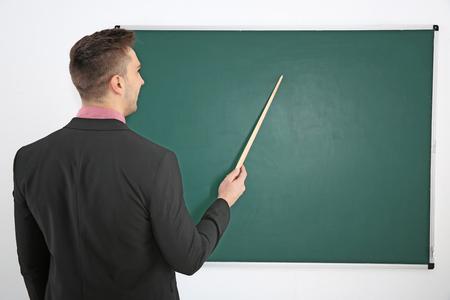 Young male teacher beside blackboard on white blackboard