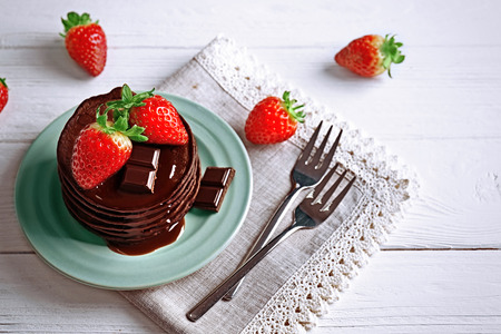 Plate with delicious chocolate pancakes and strawberry on light background