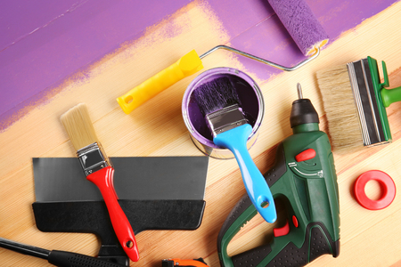 House renovation tools on purple painted wooden background