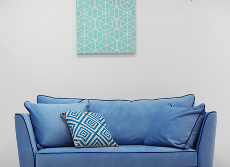 New cozy couch with pillows on light wall background