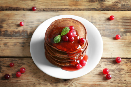 Plate with delicious chocolate pancakes and berries on wooden table