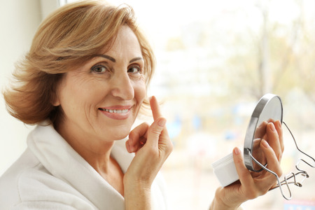 Gorgeous senior woman applying anti-aging cream on her face 写真素材