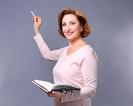 Portrait of attractive senior woman holding book and piece of chalk on grey background