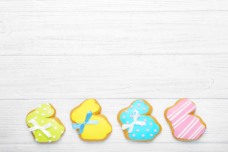 Colourful tasty Easter cookies in a row on white wooden background Stock Photo